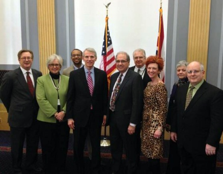 8 representatives from Philanthropy Ohio pose with Sen. Portman in front of US flag