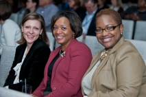 three women sitting in conference audience smiling